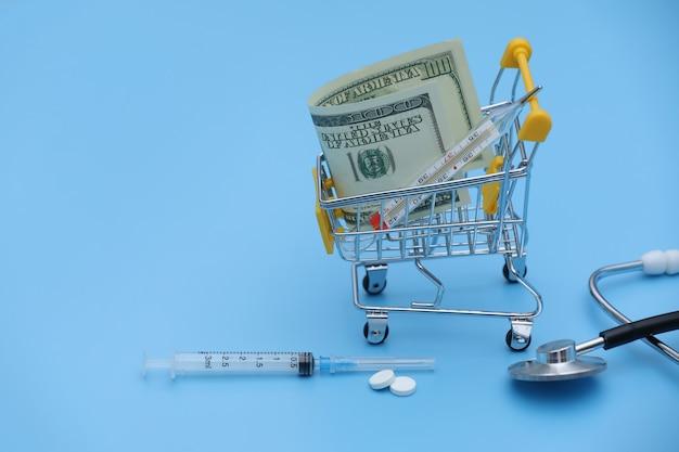 O carrinho de compras amarelo com comprimidos está em notas de dólar em um close-up azul do fundo. conceito de saúde, compras on-line, alto custo de medicamentos. remédio caro. foco seletivo