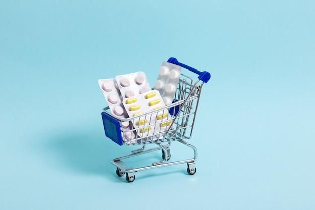 O carrinho de compras azul com comprimidos está em um close-up azul do fundo. conceito de saúde, compras on-line, alto custo de medicamentos. copie o espaço