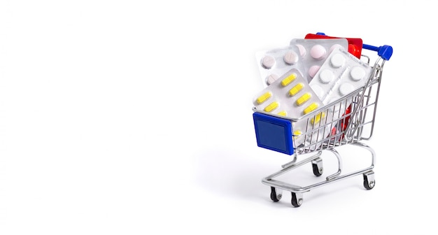 O carrinho de compras azul com comprimidos está em um close-up branco do fundo. conceito de saúde, compras on-line, alto custo de medicamentos. copie o espaço