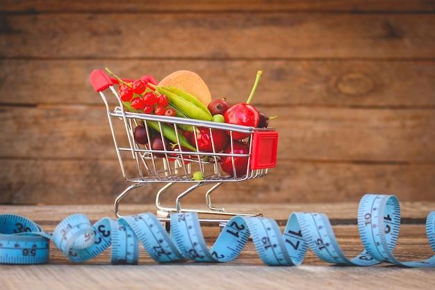 O carrinho de compras com frutos, bagas e fita alinha no fundo de madeira velho. imagem enfraquecida.