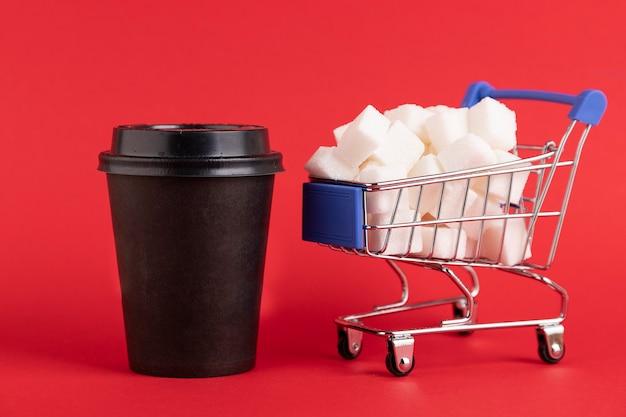 O carrinho de compras é preenchido com cubos de açúcar refinado e um copo de papel preto para café ou chá em um fundo vermelho. copie o espaço.