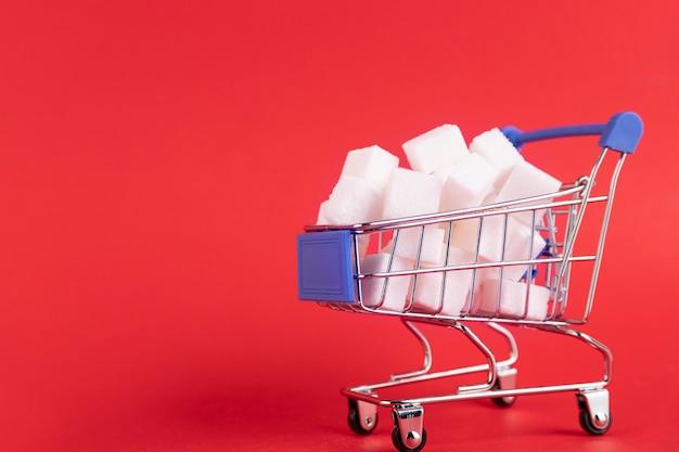 O carrinho de compras está cheio de cubos de açúcar refinado em um fundo vermelho. copie o espaço.