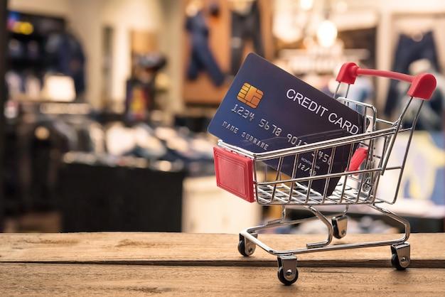 O carrinho de compras pequeno com cartão de crédito dentro e atrás é borrado. loja - conceito uso de crédito para compras.