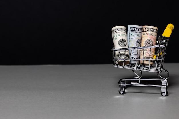 O carrinho do supermercado está cheio de dinheiro. dólares carrinhos de compras no preto