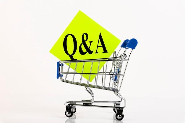 O carrinho e o texto q e a significam perguntas e respostas em papel amarelo, conceito de negócio, sobre fundo branco. copie o espaço.