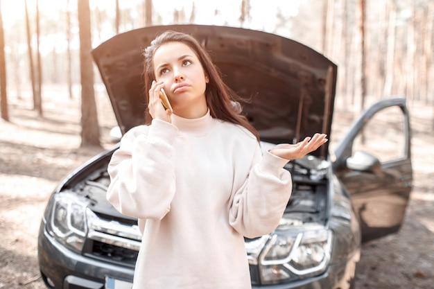 O carro avariou-se. a mulher abriu o capô e verificou o motor e outras partes do carro.