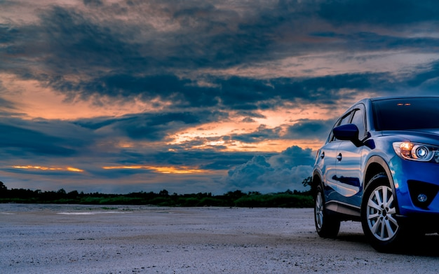 O carro azul luxuoso de suv estacionou na terra ao lado da floresta tropical com o céu bonito do nascer do sol. carro novo com esporte e design moderno. carro para viagem de aventura. indústria automobilística.