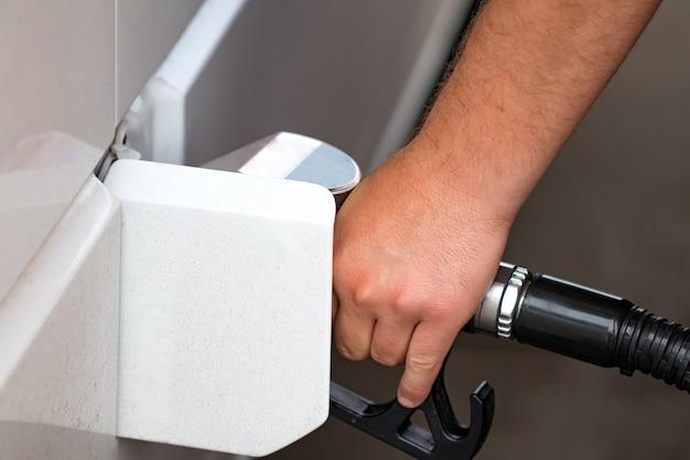 O carro branco é reabastecido em um posto de gasolina, uma pistola de reabastecimento no gargalo de um carro-tanque a gasolina.