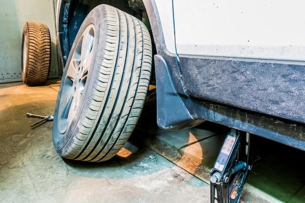 O carro com a roda desenroscada. serviço de pneus. montagem de pneu.