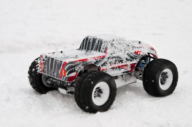 O carro controlado por rádio começa em uma estrada com neve.