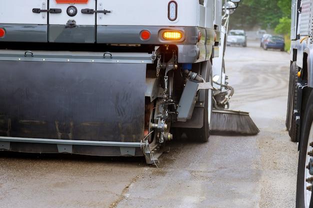 O carro da vassoura de rua está limpando a máquina no carro municipal para limpar as calçadas das estradas com escova ao ar livre.