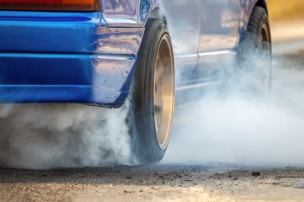 O carro de corrida de arrancada queima borracha de seus pneus em preparação para a corrida