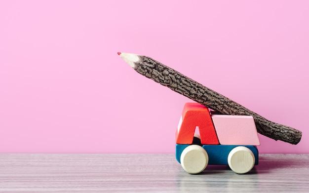 O carro de madeira do brinquedo com madeira da cor escreve no telhado. ideal para voltar ao fundo da escola