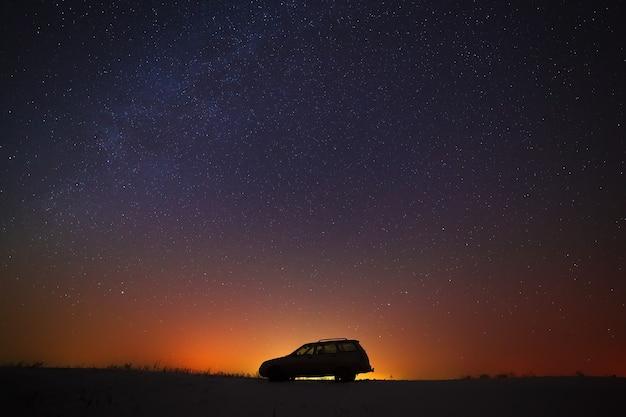 O carro do turista contra o céu estrelado.