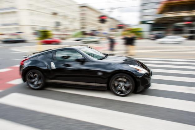 O carro esportivo preto ficou turvo no movimento da velocidade.