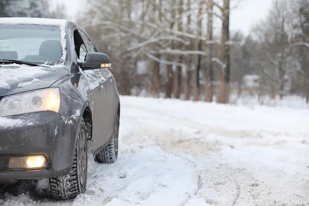 O carro está cinza na estrada na floresta. uma viagem ao campo num fim de semana de inverno. o carro na estrada em frente ao parque de inverno.