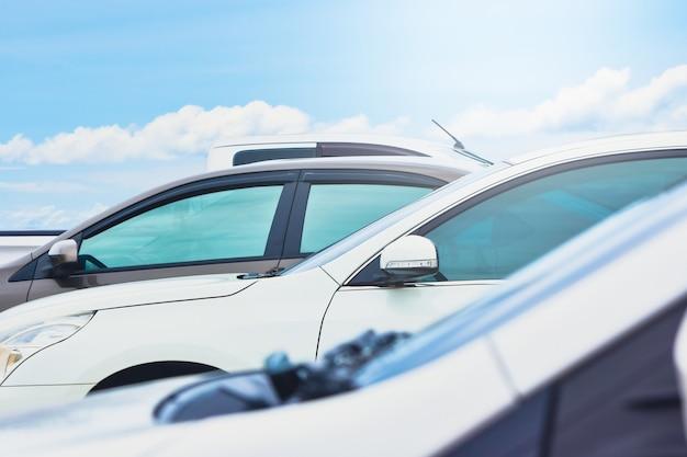 O carro está estacionado no estacionamento com uma nuvem e céu azul