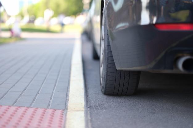 O carro está estacionado perto da faixa central amarela, close up