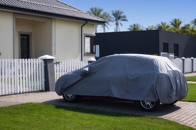 O carro está estacionado sob um dossel em um gramado com uma casa e palmeiras
