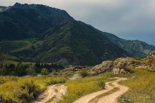 O carro está se movendo em uma estrada de terra entre montanhas e rochas