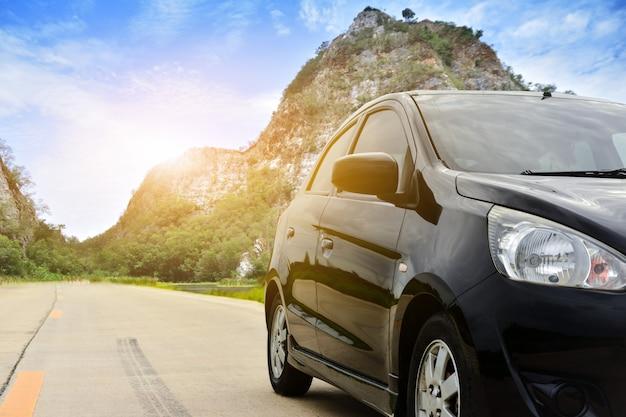 O carro estacionou na luz solar da natureza do fundo da montanha da rocha da estrada em ratchaburi tailândia