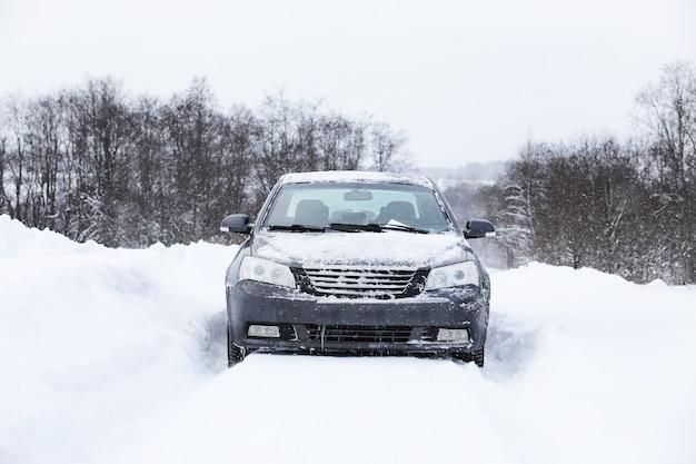 O carro fica em uma estrada coberta de neve em um dia nublado de inverno