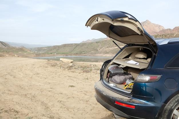 O carro fica na margem do lago com o porta-malas aberto durante o dia