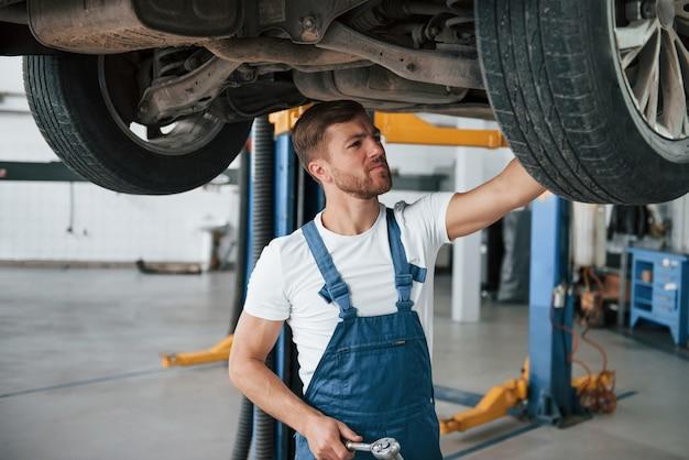 O carro moderno está sendo reparado. empregada com uniforme azul trabalha no salão automóvel.