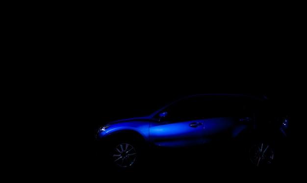 O carro novo de suv estacionou no parque de exposições. carro esportivo azul com design de luxo à noite. indústria automotiva e conceito de veículo elétrico. exposição automóvel. concessionária de carros.