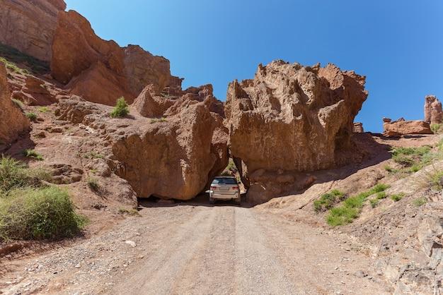 O carro passa entre duas grandes pedras no desfiladeiro charyn desfiladeiro charyn, no cazaquistão
