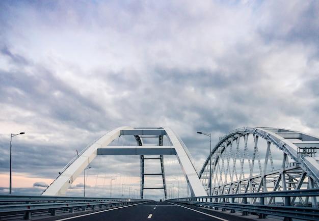 O carro passa na ponte rodoviária que conecta as margens do estreito de kerch entre taman e kerch