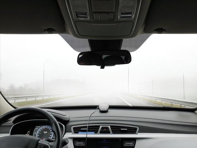 O carro passa rápido na estrada no meio do nevoeiro, vista do compartimento de passageiros