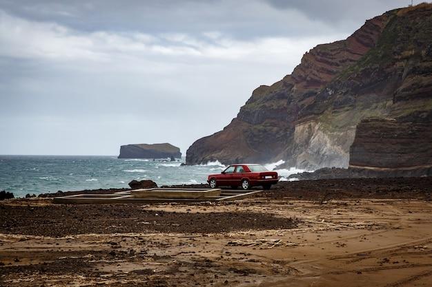 O carro perto do oceano, costa rochosa.