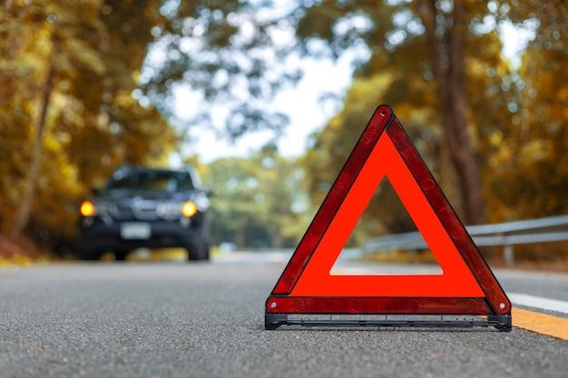 O carro preto tem um parque de acidentes na estrada.