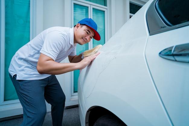 O carro que detalha, homem no uniforme azul limpa um carro branco à disposição que guarda um carro grande de lavagem do microfiber.
