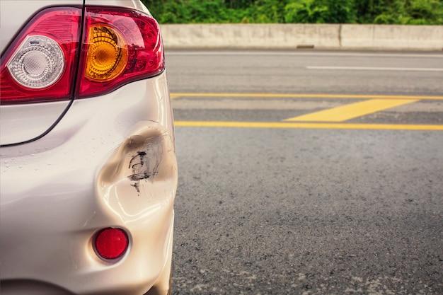 O carro tem o para-choque traseiro amassado e danificado após acidente