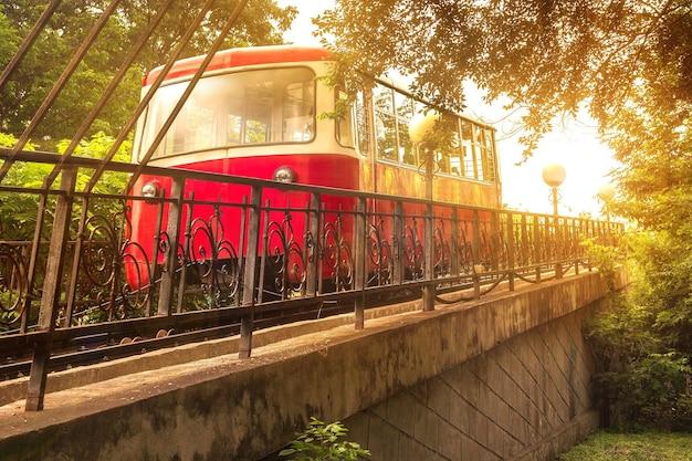 O carro vermelho do funicular sobe à luz do sol de um pôr do sol na capital do extremo oriente russo, vladivostok.
