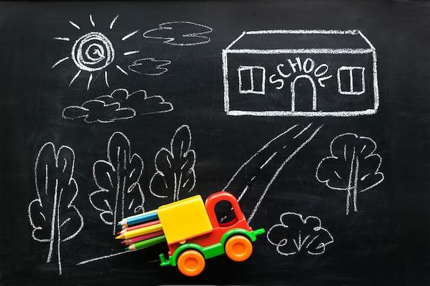 O carro vermelho e amarelo do brinquedo leva lápis coloridos à casa da escola