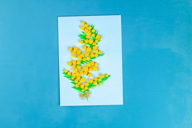 O cartão de diy com mimosa floresce as bolas de papel para o 8 de março no fundo azul.