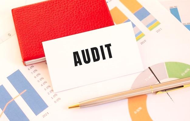 O cartão de visita branco com o texto audit encontra-se ao lado do porta-cartões de visita vermelho e gráficos