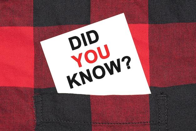 O cartão de visita branco com o texto você sabia encontra-se na manga de uma camisa quadriculada.