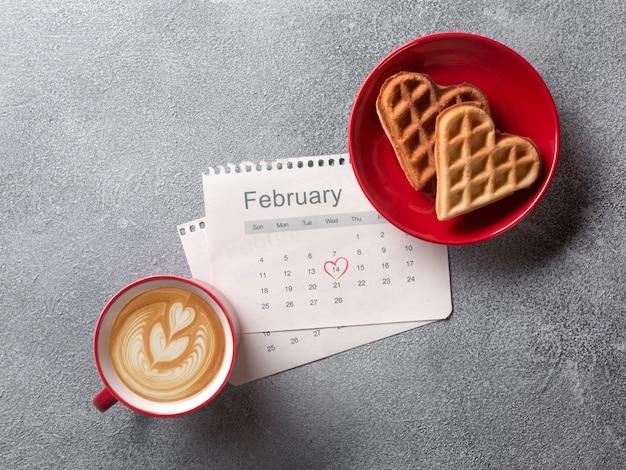O cartão do dia de valentim com copo de café e coração deu forma a cookies no fundo cinzento.