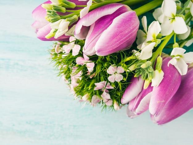 O cartão roxo vazio floresce o fundo da cor pastel da mola das rosas das tulipas.