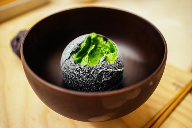 O carvão revestiu uma bola de sorvete caseiro de chá verde no café de sobremesa japonês. sobremesa saborosa fusão exótica em estilo asiático ..