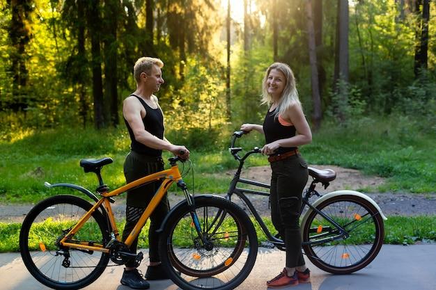 O casal apaixonado de bicicleta na floresta do parque