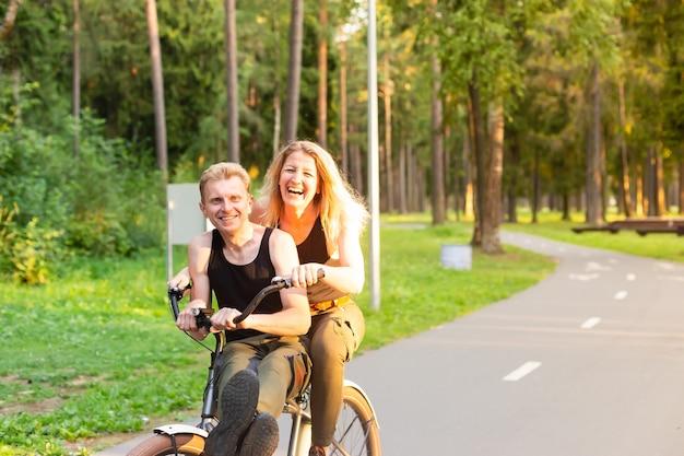 O casal apaixonado de bicicleta se divertindo no parque