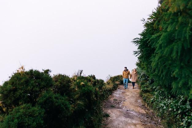 O casal apaixonado de mãos dadas e sobe a estrada de terra