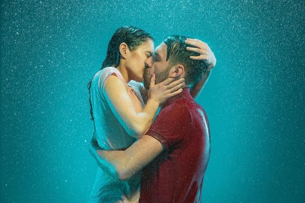 O casal apaixonado se beijando na chuva em um fundo turquesa