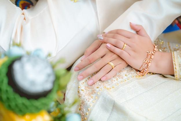 O casal asiático de mãos dadas juntos no dia do casamento