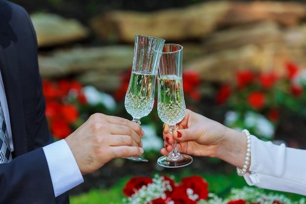 O casal bebendo champanhe no parque